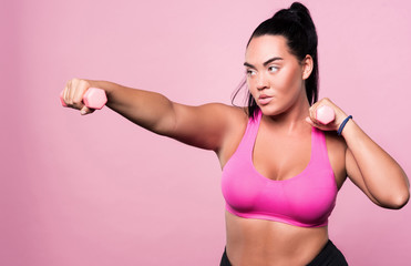Plump concentrated woman doing sport exercises