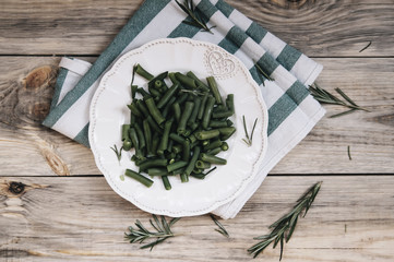 Delicious fresh green beans with rosemary decoration on the wooden table background