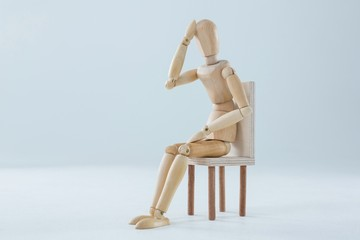 Tired wooden figurine with hand on forehead