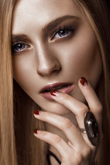 Beautiful blond woman with healthy skin and hair, red manicure, posing in studio. Beauty face