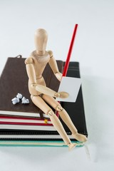 Wooden figurine sitting on a pile of books writing on a paper