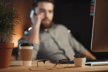 Designer working while talking by phone near glasses and coffee
