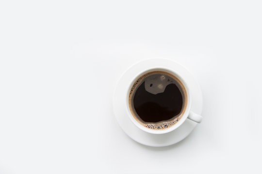 Christmas and winter concept. White mug of hot black coffee on white background. Top view.