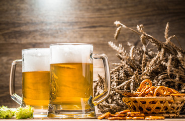 Mugs with beer foam with pretzels, hops and wheat