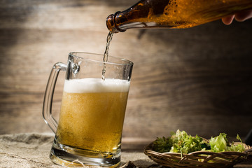 On wooden background beer flows from bottle in mug