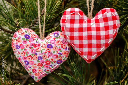 Two Hearts Made By Hand Hanging On A Green Christmas Tree