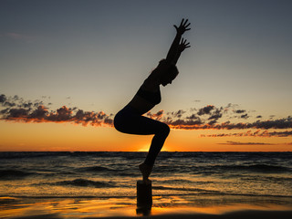 Peaceful landscape with a young woman in the beach at sunset practicing yoga - balanced on a small stump hands outstretched towards the sky.