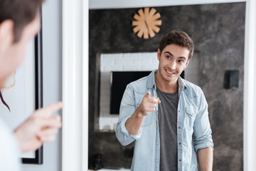 Smiling young man pointing finger at his mirror reflection