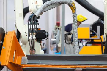Industrial welding robot arm, blurred welder in the background