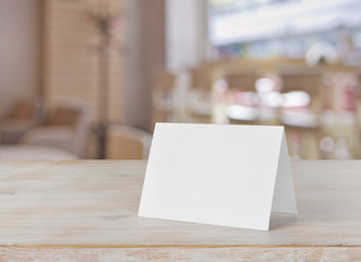 Blank paper table card on wooden table over bar background