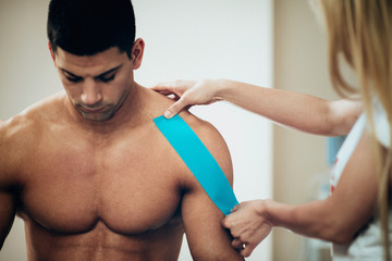 Kinesio tape. Physical therapist using kinesio tape