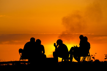 people in camping sitting near campfire against sunset