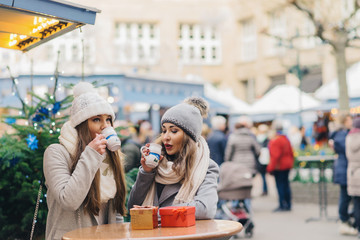 two female best friends drinking mulled wine on christmas deco o