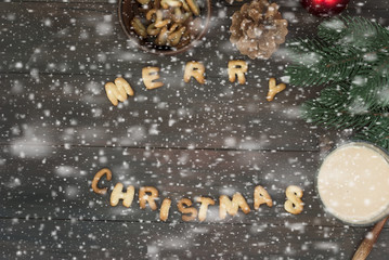 Merry Christmas word written with biscuit letters on wooden tabl