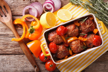 Ballotine rabbit baked with tomatoes, pepper and rosemary close up in baking dish. Horizontal top view