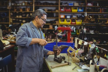 Shoemaker hammering on a shoe