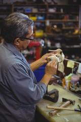 Shoemaker examining a high heel in workshop