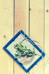 Craft supplies. Blue photo frame, boxwood, cone and rope on light wooden pine background. Coloring and processing photo