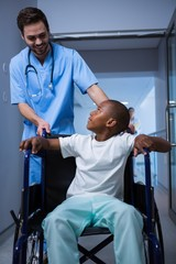 Male nurse interacting with child patient in corridor
