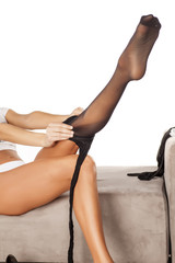 woman sitting on the bed and pull on the black tights