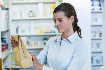 Pharmacist looking at medicine package
