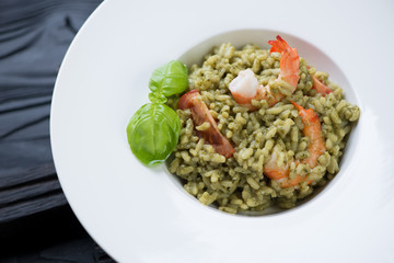 Close-up of a white plate with spinach and tiger shrimps risotto