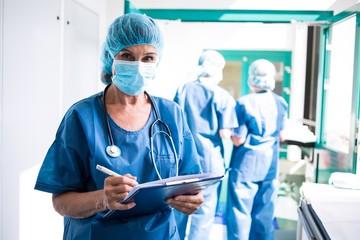 Female surgeon writing on clipboard in corridor