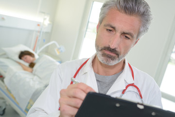 portrait of handsome doctor writing on clipboard