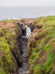 Waves crashing on large rocks at Hook Head, Wexford, Republic of Ireland.
