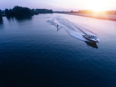 Man water skiiing on lake behind a boat