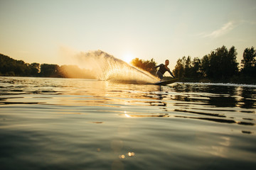 Wakeboarder moving fast in splashes of water Wall mural