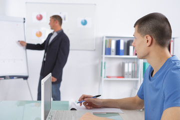 teacher with notepad showing scheme on white board in classroom