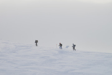 Group of people hiking in winter mountains during a snow storm