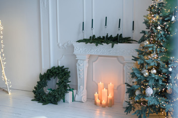 Christmas tree with decorations and lights in living room with fireplace and candles