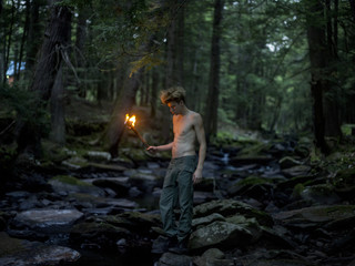 Barechested man carrying flame torch in forest