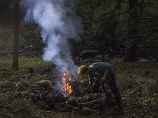 Man tending fire in forest