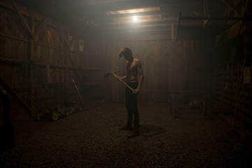 Bare chested man standing in dark barn holding  pickaxe