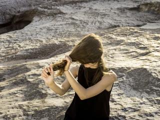 Girl standing on beach pulling hair over face
