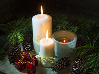 Candles with fir cones and pine branches. Christmas decorations.