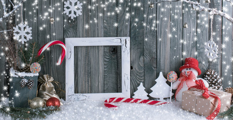 Christmas interior with snowman, photo frame, decorative branches, gifts