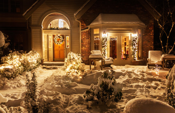 Home front entrance on a snowy night decorated for Christmas