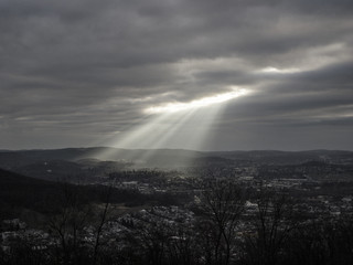 Sun breaking through clouds, shining on rural town, black and white Fototapete