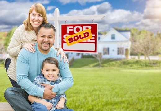Happy Mixed Race Hispanic and Caucasian Family Portrait In Front of House and Sold For Sale Real Estate Sign.