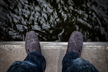 Suicide concept., Depressed young man looking down at his shoe and contemplating suicide., On the edge of a bridge with river below.