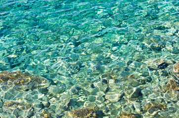 Rocky sea floor visible thru crystal clear turqoise water of Aegean sea in Greece