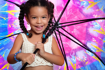 Funny african american small girl holding a huge colorful umbrella