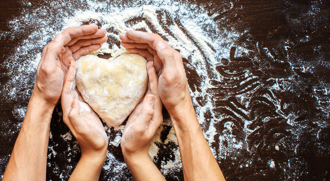 Hands of men and women make dough heart. The symbols of protecti
