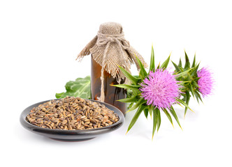 Milk thistle oil with flowers and seeds.