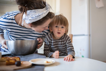 young pregnant mother   with son Toddler, make  dough for baking