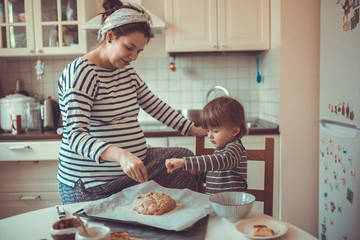 young pregnant mother  making bread with her son Toddler toning,